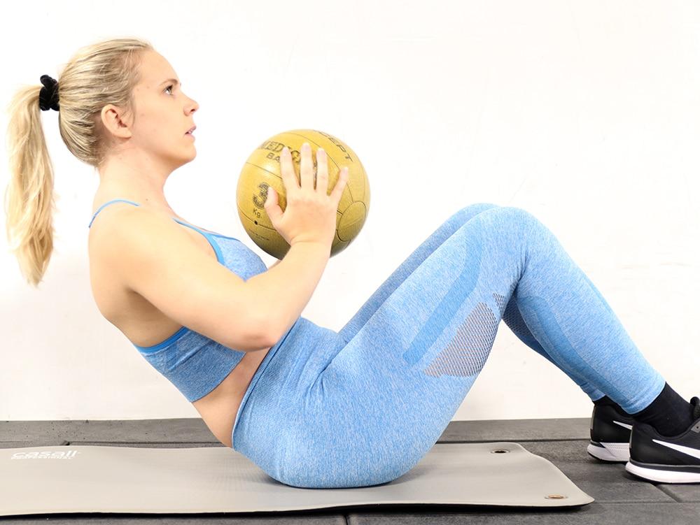 träna mage på gymmet med medicinboll